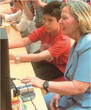Η κυρία Αμαλία Μαστρογιάννη, 72 ετών, πρώην μετανάστρια στη Γερμανία, καθοδηγούμενη από τον 13χρονο Μάριο, βλέπει στην οθόνη του υπολογιστή μέσω της εφαρμογής Google Εarth το σπίτι όπου διέμενε στο Μόναχο: εμφανείς η χαρά και η συγκίνησή της